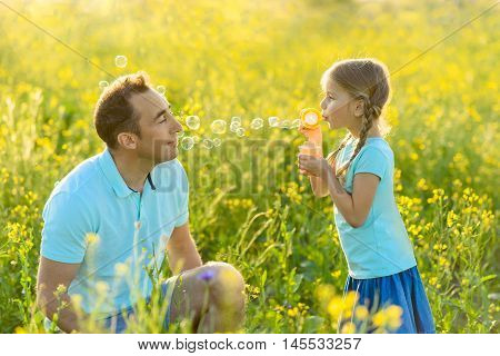 Dad is the best. Happy father playing with his little daughter while she blowing bubbles outdoors in nature