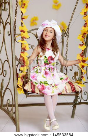 Cheerful little girl in a white dress with roses and a white hat. Girl swinging on an old swing.