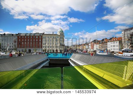 Copenhagen Denmark - August 15 2016: View on docks Nyhavn people and colorful architecture from bridge Inderhavnsbroen - Inner Harbour pedestrian and cyclist bridge in Copenhagen Denmark