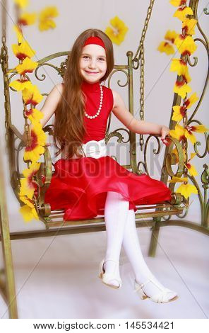 Smiling little girl with long brown hair to her waist . Girl in bright red dress swinging on a swing