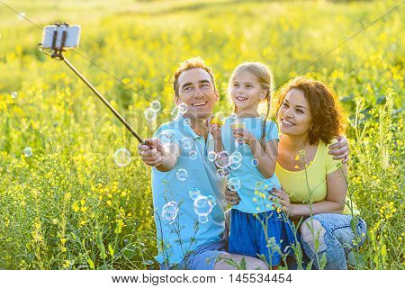 Love is in air. Happy young family making selfie in nature, using smartphone and cheerfully smiling