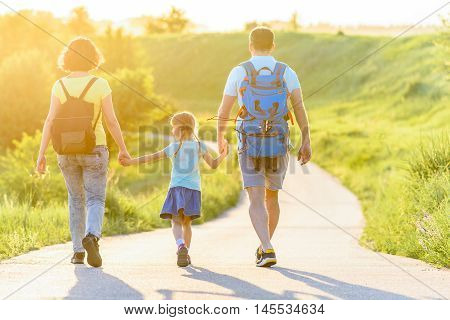 Enjoying nature hike together. Rear view shot of young family walking along road with backpacks and holding hands