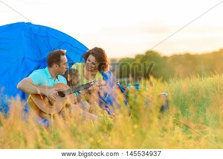 Making music in outdoors. Cute young family spenting their holidays outside on picnic with guitar and sitting near blue tent
