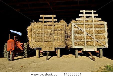 An old orange tractor and two loaded hayracks full of grain bundles are parked in the entrance of a steel shed