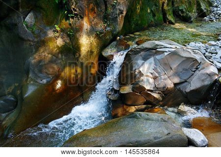 Little wondrous waterfall among the rocks in a mountain forest