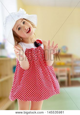 Joyful little girl in a very short polka dot dress and white Panama city beach , claps.Close-up.Against the background of a child's room , concept of education and family values.