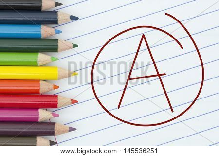 Being an A grade student Pencil Crayons with loose leaf paper and a grade A