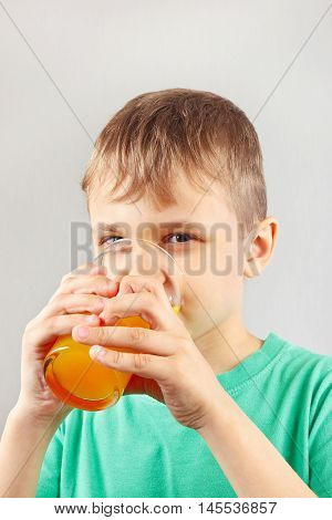 Little blonde boy drinking a fresh citrus juice