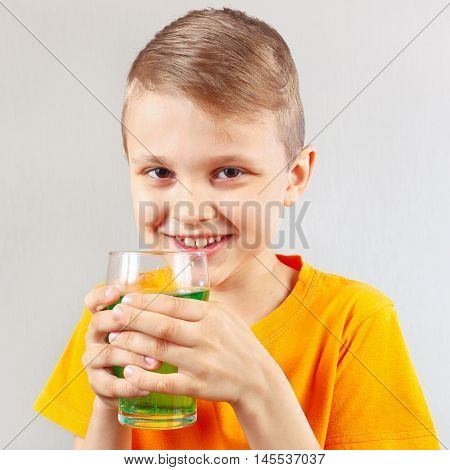 Little funny boy with a glass of green lemonade