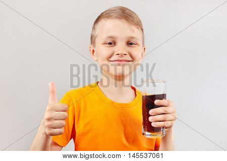 Little smiling boy with a glass of fresh cola