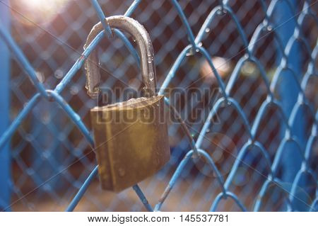 close up a key lock hook on iron wire gates and water drop of rain with blur background selective focus filtered image light and flare effect added