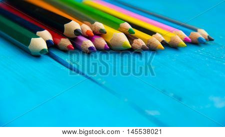 Colored pencils on a wooden background. Copy space