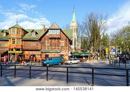 ZAKOPANE, POLAND - MAY 8, 2016: Old wooden inn and church in Krupowki Street in Zakopane, Poland.