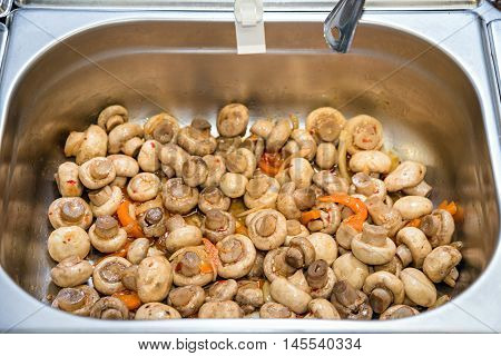 Champignons in metal bowl. Mushrooms salad. Special recipe for marinated champignons. Enjoy the taste.