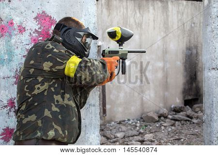 man in camouflage with a paintball gun in his hand