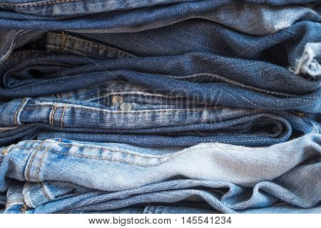Pile of clothes made of a collection of colorful blue jeans