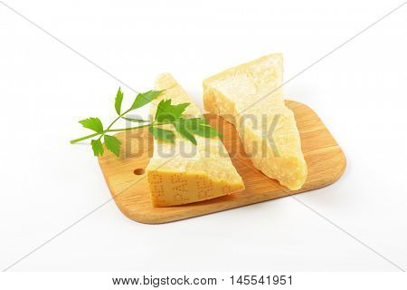 Two wedges of true Parmesan cheese on cutting board