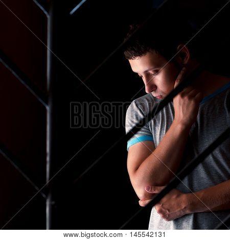 sad man behind bars thinking about something
