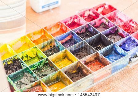 The Watercolor colorful box sloppy on table background.