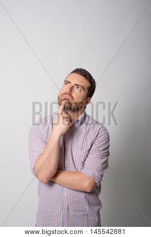 Doubtful face expresison man isolated on gray background