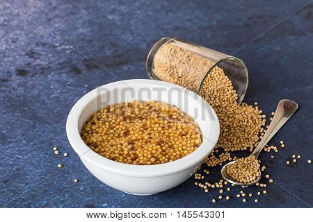 White cup cooked mustard, a glass and a spoon with mustard seeds on a blue background.