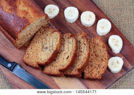 Homemade banana cake with sliced banana on butcher served.