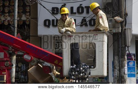 Hanoi, Vietnam - Aug 30, 2016: Asian electrician workers repairing the electric and lighting system in occasion of big holiday in Hanoi capital city, Vietnam.