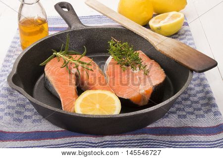 raw scottish salmon steak with lemon thyme and rosemary in a cast iron pan