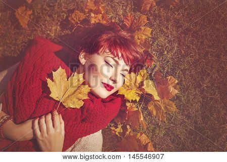 Beautiful young woman with red hair holding yellow maple leaf lying on the ground. Outdoor shot. Fall. Copy space.