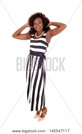 A gorgeous young African American woman standing in a black and white jumpsuit with hands on head isolated for white background.