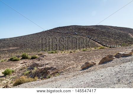 The Ramon Crater climbing up the hill in Makhtesh Ramon nature reserve in Negev desert Israel
