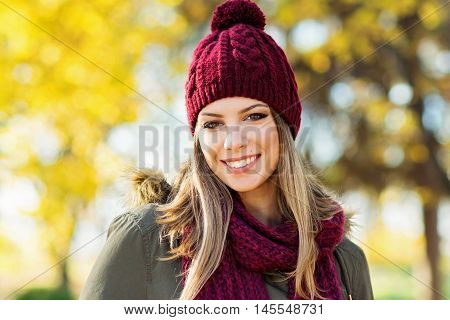 Closeup portrait of gorgeous young blonde Caucasian woman in knitted beanie and scarf in autumn in park. Young woman head shot, natural light, retouched, vibrant colors.