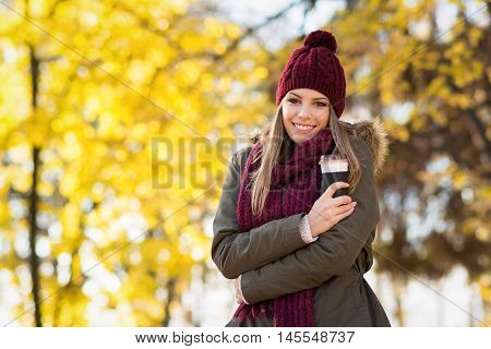 Beautiful blonde young woman in jacket, beanie hat and scarf in park in autumn holding takeaway coffee cup, smiling. Natural light, medium retouch, vibrant colors, copy space.