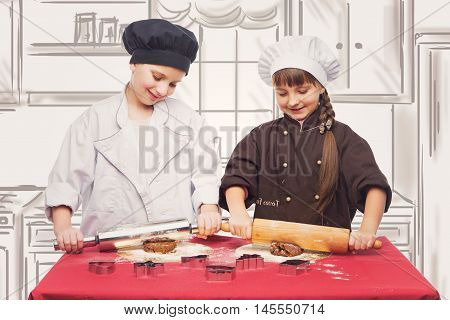 Beautiful boy and girl in chef clothes making christmas cookies with plunger. Children over kitchen drawing background.