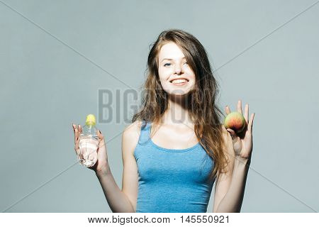 Beautiful girl with long hair in blue undershirt holds water bottle apple and smiles on grey wall