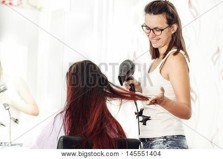 Red hair young woman at hairdresser. Ombre style.