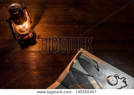 Old-fashioned kerosene lamp, map and accessories on the dark table in twilight. Soft focus