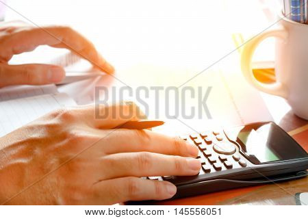 savings finances economy and home concept - close up of man with calculator counting making notes at home soft focus.