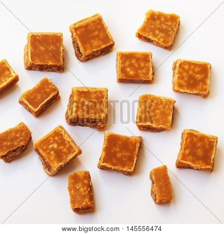 Caramel candies over white background. Golden Butterscotch toffee caramel