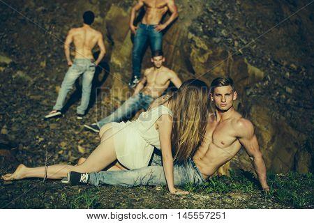 four handsome young macho men with muscular sexy body and six packs on torso in jeans and pretty woman in white dress sunny day outdoor on stony natural background