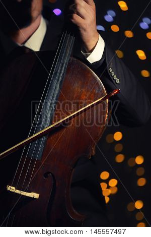 Man playing cello in darkness on blurred lights background