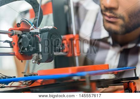 Close up of young man using 3d printer for prototyping