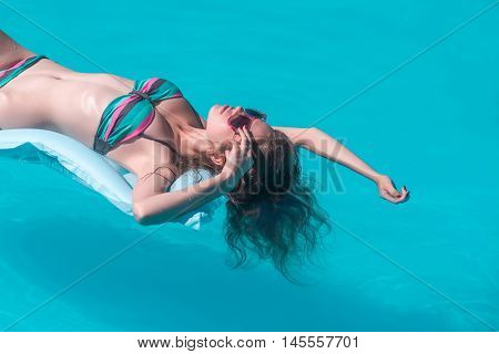 Young Girl Tanning In Pool