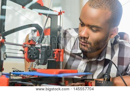 Serious young man is watching 3d printer work with interest in office