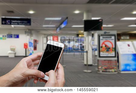 Human holding blank screen of smart phone and waiting departures time background blur.