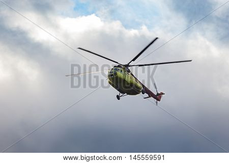 Green helicopter on a background cloudy sky