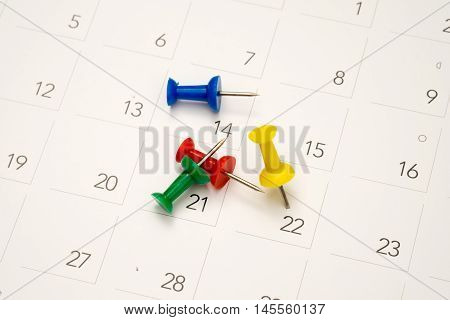 Colourful pushpin on calendar for important date.