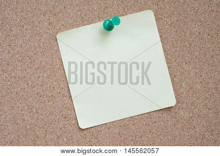 Yellow sticker pinned green pushpin with cork background.