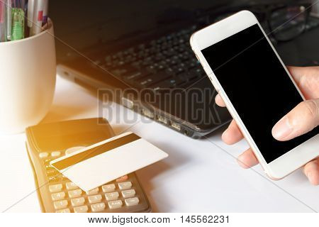 Online payment man's hands using smart phone for online shopping on the desk in the office or home