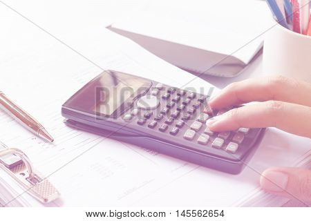 Financial data analyzing. Close-up photo of a businessman's hand counting on calculator in office or home. Soft focus